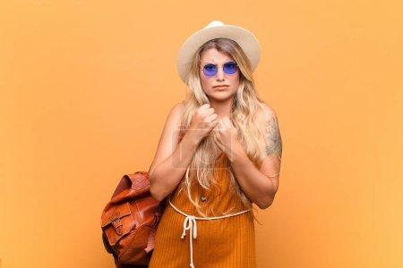 Photo pour Jeune jolie femme latine à l'air confiante, en colère, forte et agressive, avec les poings prêts à se battre en position de boxe. concept touristique - image libre de droit