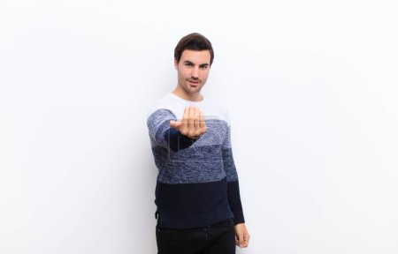 Photo for Young handsome man feeling happy, successful and confident, facing a challenge and saying bring it on! or welcoming you against white wall - Royalty Free Image
