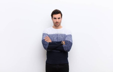 Photo for Young handsome man feeling displeased and disappointed, looking serious, annoyed and angry with crossed arms against white wall - Royalty Free Image