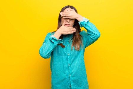 Photo pour Jeune jolie femme couvrant le visage avec les deux mains en disant non à la caméra ! refuser les photos ou interdire les photos contre le mur orange - image libre de droit