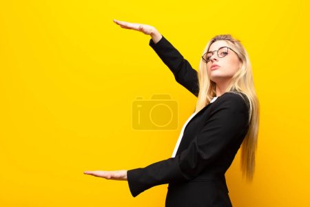 Photo for Young pretty blonde woman holding an object with both hands on side copy space, showing, offering or advertising an object against yellow wall - Royalty Free Image