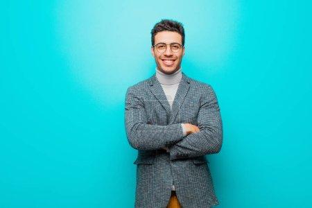 Photo pour Jeune homme arabe ressemblant à un sourire joyeux, fier et satisfait achiever avec les bras croisés contre le mur bleu - image libre de droit