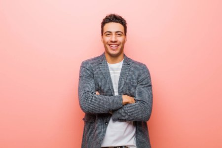 Photo for Young arabian man looking like a happy, proud and satisfied achiever smiling with arms crossed against pink wall - Royalty Free Image