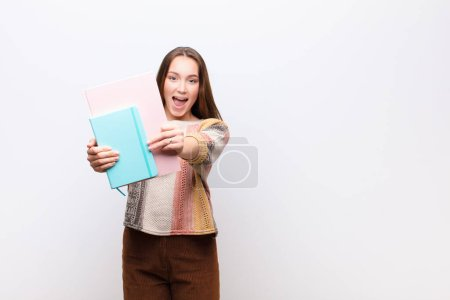 Photo for Young blonde pretty girl with books against white wall - Royalty Free Image