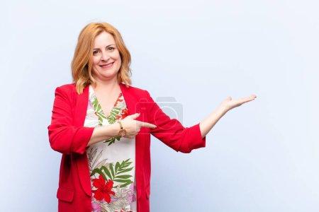 Photo pour Femme d'âge moyen souriant, se sentant heureux, insouciant et satisfait, pointant vers le concept ou l'idée sur l'espace de copie sur le côté - image libre de droit