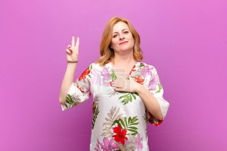 Photo pour Middle age woman looking happy, confident and trustworthy, smiling and showing victory sign, with a positive attitude - image libre de droit