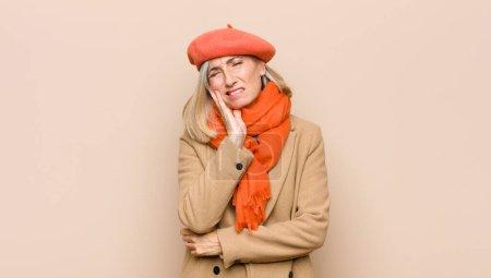 Photo pour Senior ou d'âge moyen jolie femme tenant la joue et souffrant mal aux dents douloureux, se sentant malade, malheureux et malheureux, à la recherche d'un dentiste - image libre de droit