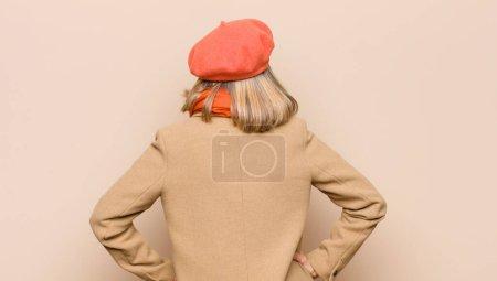 Photo pour Senior ou d'âge moyen jolie femme se sent confus ou plein ou doutes et questions, se demandant, avec les mains sur les hanches, vue arrière - image libre de droit