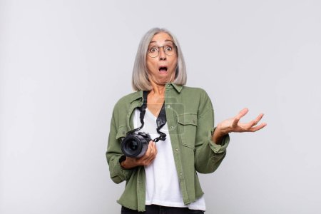 middle age woman open-mouthed and amazed, shocked and astonished with an unbelievable surprise. photographer concept