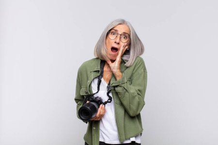 middle age woman feeling shocked and scared, looking terrified with open mouth and hands on cheeks. photographer concept