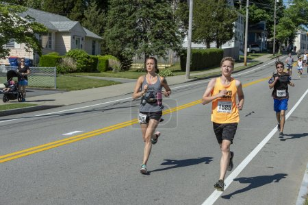 Fairhaven, Massachusetts, USA - June 17, 2018: Long strides at the bottom of a hill as runners hit the one mile mark in the Fairhaven Father's Day Road Race