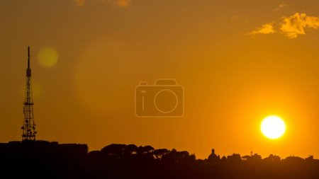 Rome at sunset timelapse with the fiery orb of the sun dropping below the horizon above the rooftops of the historical buildings. view from the Pincio Landmark with tv tower