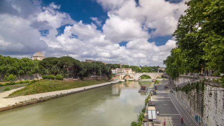 Photo pour Isola tiberina timelapse hyperlapse est la plus grande île du fleuve tibera à rome. Cette petite île est attrayant endroit touristique en route vers le quartier de trastevere. Vue du pont avec ciel nuageux - image libre de droit
