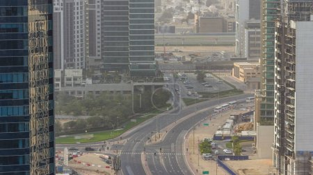 Photo pour La baie de Dubaï entreprise tours à jour temps aériennes timelapse. Vue sur les toits des gratte-ciels et les nouvelles tours en construction. Circulation sur la route - image libre de droit