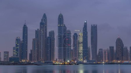 Photo for Panorama of modern skyscrapers in Dubai city night to day transition timelapse from the Palm Jumeirah Island. Dubai, United Arab Emirates. Dubai marina and JBR in clouds at early morning - Royalty Free Image
