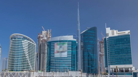 Photo for Panoramic timelapse view of business bay and downtown area of Dubai. Modern skyscrapers, green grass and blue sky - Royalty Free Image