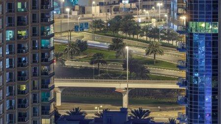 Photo pour Marina de Dubaï à timelapse de la nuit, les lumières étincelantes et les plus hauts gratte-ciels. Circulation sur la route entre les deux tours - image libre de droit