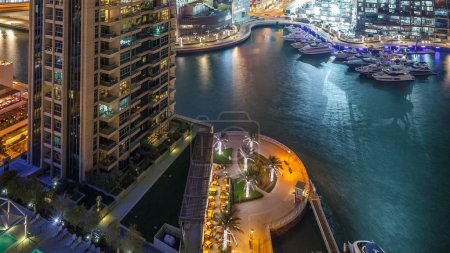 Photo pour Plus haut gratte-ciel de Dubaï Marina à timelapse de la nuit, les lumières étincelantes et éclairage de soirée. Trafic sur la route et les palmiers sur la promenade - image libre de droit