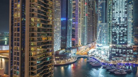 Photo for Tallest skyscrapers in Dubai Marina at night timelapse, Glittering lights and evening illumination. Traffic on the road and palms on promenade - Royalty Free Image