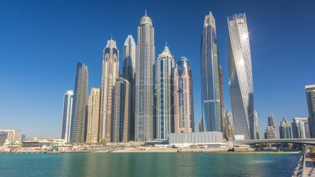 Scenic view of Dubai Marina tallest Skyscrapers with boats timelapse, Skyline, View from sea, United Arab Emirates. Blue sky at sunny day