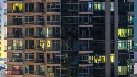 Photo for Glowing windows of skyscrapers at night timelapse. View of modern residential high-rise buildings in Dubai marina. People moving inside. Aerial top view. Pan up - Royalty Free Image