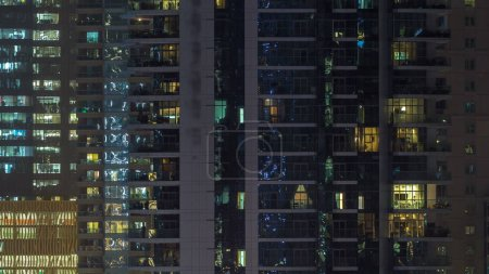 Photo for Glowing windows of skyscrapers at night timelapse. View of modern residential and office high-rise buildings in Dubai marina. People moving inside. Aerial top view. Zoom in - Royalty Free Image