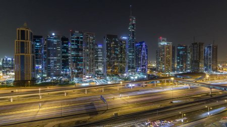 Photo for Aerial view of Jumeirah lakes towers with illuminated skyscrapers night timelapse with traffic on sheikh zayed road and metro line. Rooftop view from Dubai marina - Royalty Free Image