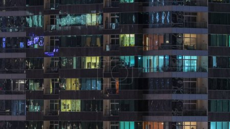 Photo for Windows of the multi-storey building of glass and steel lighting inside and moving people within timelapse. Aerial view of modern residential skyscrapers in Dubai. - Royalty Free Image