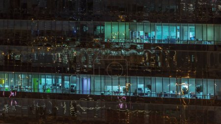 Photo pour Fenêtres de l'immeuble de plusieurs étages de verre et d'acier, éclairage à l'intérieur et au déplacement de personnes au sein de timelapse. Vue aérienne de gratte-ciels de bureaux modernes à Dubaï. Pan droit - image libre de droit