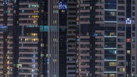 Photo pour Fenêtres de l'immeuble de plusieurs étages de verre et d'acier, éclairage à l'intérieur et au déplacement de personnes au sein de timelapse. Vue aérienne du gratte-ciel résidentiels modernes à Dubaï. Pan vers le haut - image libre de droit