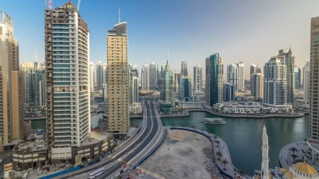 Photo for Amazing colorful dubai marina skyline during sunset timelapse. Great perspective of multiple tallest skyscrapers of the world with yachts and boats. Sunlight over buildings. United Arab Emirates. - Royalty Free Image