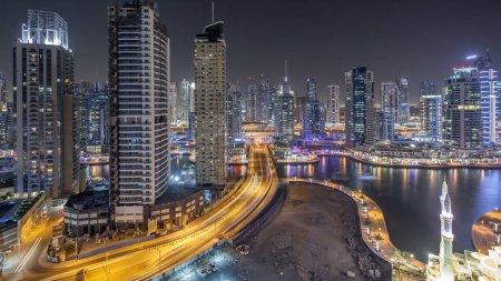 Photo pour Tours résidentielles avec éclairage et l'illumination timelapse. Canal d'eau et promenade sur la skyline de Dubai Marina pendant la nuit. Flottant d'yachts et bateaux de traite près de gratte-ciels - image libre de droit