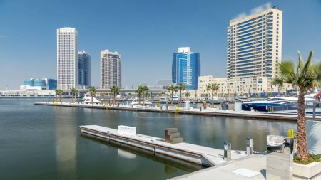 Photo for Panoramic timelapse view of business bay and downtown area of Dubai. Modern skyscrapers reflected in water and blue sky. View from promenade on embankment with yachts and boats - Royalty Free Image
