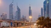 """Постер, картина, фотообои """"Движение на перекрестке и мост на Sheikh Zayed Road, в окружении день небоскребов ночь перехода timelapse. Вид сверху в Дубае на вечер, Объединенные Арабские Эмираты"""""""