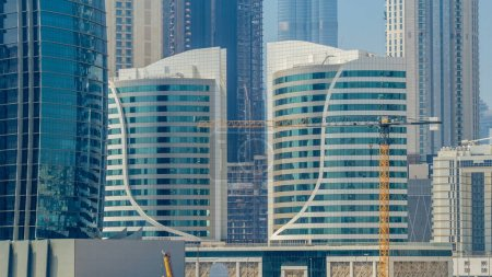 Photo for Panoramic timelapse view of business bay and downtown area of Dubai. Modern skyscrapers and blue sky at sunny day. View from promenade on embankment - Royalty Free Image