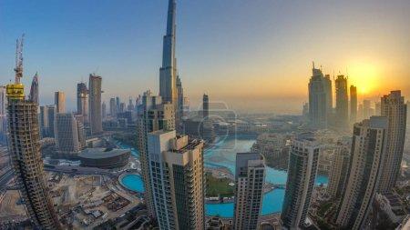 Photo pour Lever du soleil de matin brumeux dans le centre-ville de Dubaï timelapse. Vue sur les gratte-ciel de la ville futuriste couvert dans la brume. Vue aérienne de sur le toit avec des tours modernes. Dubaï, Émirats Arabes Unis - image libre de droit