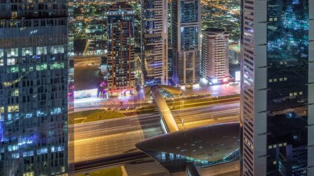 Photo for Skyline view of the buildings of Sheikh Zayed Road and DIFC night timelapse in Dubai, UAE. Illuminated skyscrapers in financial centre aerial view from above with metro station - Royalty Free Image