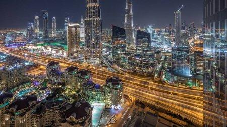 Photo pour Dubai skyline du centre-ville nuit timelapse avec le plus haut bâtiment et l'autoroute la circulation routière, Émirats Arabes Unis. Vue aérienne du toit du gratte-ciel illuminés tours modernes - image libre de droit