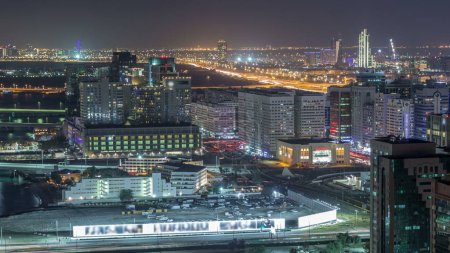 Photo for Aerial skyline of Abu Dhabi city centre from above night timelapse with illuminated skyscrapers with traffic on road - Royalty Free Image
