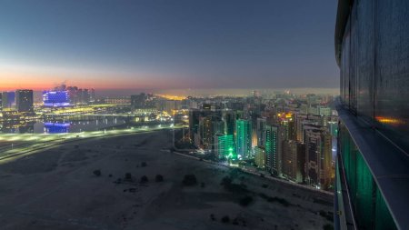 Photo for Abu Dhabi city skyline with illuminated skyscrapers before sunrise from above night to day transition timelapse. Aerial view at foggy morning from rooftop with reflection from glass surface - Royalty Free Image