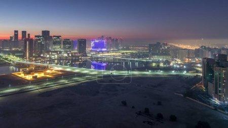 Photo pour Skyline de la ville d'Abu Dhabi avec des gratte-ciel éclairés avant le lever du soleil de la nuit au jour passage timelapse. Vue aérienne au matin brumeux depuis le toit - image libre de droit