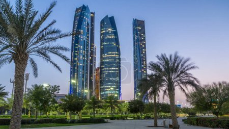 Photo for Skyscrapers of Abu Dhabi illuminated with Etihad Towers buildings day to night transition timelapse. Abu Dhabi is the capital and the second most populous city of the United Arab Emirates - Royalty Free Image