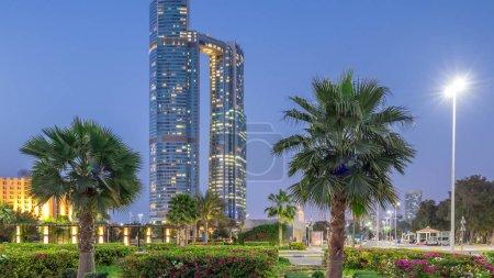 Photo pour Gratte-ciel d'Abou Dhabi, éclairé par la Nation tours bâtiments jour à nuit transition timelapse. Palmiers dans l'éclairage de parc et de la rue - image libre de droit