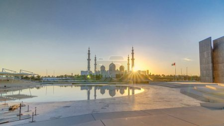 Sheikh Zayed Grand Mosque in Abu Dhabi at sunset timelapse, UAE. Evening view from Wahat Al Karama with reflections on water