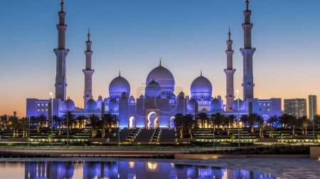 Sheikh Zayed Grand Mosque in Abu Dhabi day to night transition timelapse after sunset, UAE. Evening view from Wahat Al Karama with reflections on water