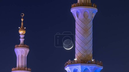 Photo for Sheikh Zayed Grand Mosque illuminated at night timelapse, Abu Dhabi, UAE. Minarets with moon crescent. The 3rd largest mosque in the world - Royalty Free Image