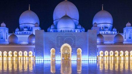 Photo pour Grande mosquée Cheikh Zayed illuminée la nuit timelapse, Abu Dhabi, EAU. Cour intérieure avec des reflets sur le sol. La 3ème plus grande mosquée du monde - image libre de droit