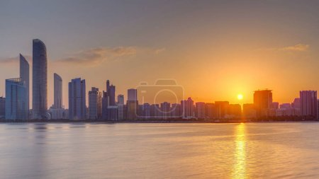 Photo for Abu Dhabi city skyline on sunrise time with water reflection timelapse from the Breakwater near cultural village. Few clouds on morning sky - Royalty Free Image