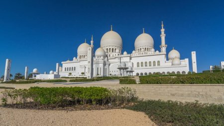 Photo pour Sheikh Zayed Grand mosquée timelapse hyperlapse à Abu Dhabi, la ville capitale des Émirats Arabes Unis. Face arrière avec des arbres. Ciel bleu à jour ensoleillé - image libre de droit