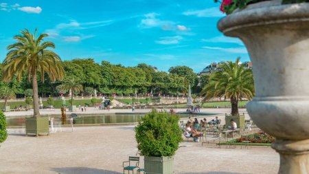 The beautiful view of the Luxembourg Gardens timelapse with fountain in Paris, France. Blue cloudy sky at summer day.